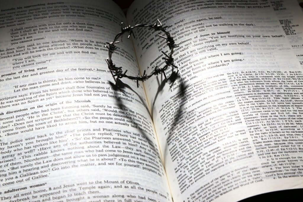 crown of thorns makes aheart shape shadow on an open Bible